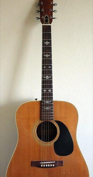 Акустическая гитара с наклейками на грифе