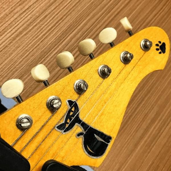 Нанести наклейку котенок на головы грифа гитары